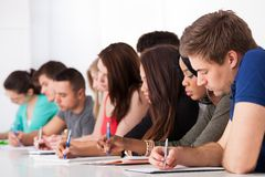 Row of college students writing at desk Stock Image