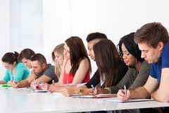 Row of college students writing at desk Royalty Free Stock Photo