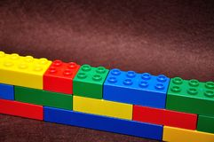Row of color building blocks built as a wall. A row of color building blocks built as a wall royalty free stock photography