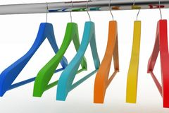 Row of color coat hangers on metal clothes rail Stock Photo
