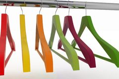 Row of color coat hangers on metal clothes rail Royalty Free Stock Images
