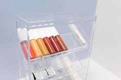 A row of color lipsticks and nail coating on transparent acrylic royalty free stock image