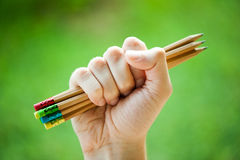 Row of color pencils in hands on green bush Royalty Free Stock Images