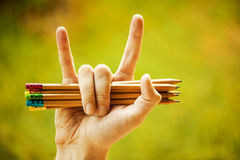Row of color pencils in hands on green bush Royalty Free Stock Photos