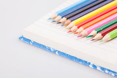 Row of color pencils on a notebook Royalty Free Stock Photography