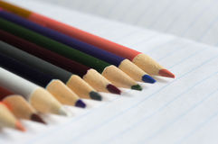 A row of color pencils on an open writing-book Stock Photo
