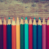 Row of colored drawing pencils closeup on old desk. Stock Images