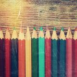 Row of colored drawing pencils closeup on old desk Royalty Free Stock Photography