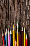Row of colored drawing pencils closeup on old grunge natural woo Royalty Free Stock Image