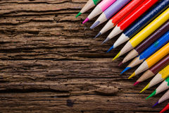 Row of colored drawing pencils closeup on old grunge natural woo. Den shabby desk background. Vintage stylized image. Copy space Royalty Free Stock Image