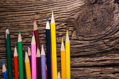 Row of colored drawing pencils closeup on old grunge natural woo Stock Photo