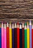 Row of colored drawing pencils closeup on old grunge natural woo Stock Image