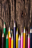 Row of colored drawing pencils closeup on old grunge natural woo Stock Photography