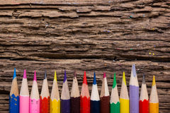 Row of colored drawing pencils closeup on old grunge natural woo. Den shabby desk background. Vintage stylized image. Copy space Royalty Free Stock Photo