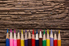 Row of colored drawing pencils closeup on old grunge natural woo. Den shabby desk background. Vintage stylized image. Copy space Stock Image