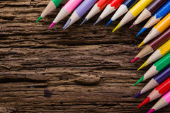 Row of colored drawing pencils closeup on old grunge natural woo Stock Photos