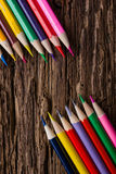Row of colored drawing pencils closeup on old grunge natural woo Stock Images