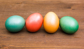 Row of colored eggs on wood Royalty Free Stock Photo