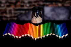 A row of colored pencils lined up in a wavy pattern with a blurry background and an electirc pencil sharpener full stock images