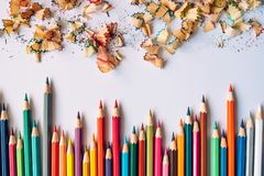 Row of colored pencils and pencil shaves on a paper stock photo