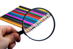 Row of colored pencils. Under a magnifying glass close-up on white Royalty Free Stock Photography