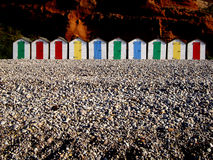 Row of colorful beach huts. Row of colorful huts on a rocky beach in Budleigh Salterton, Devon, England Royalty Free Stock Photography