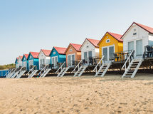 Row of colorful beach huts in the sand Stock Images