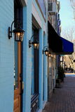 Row of colorful blue storefronts on cobblestone sidewalk Stock Image