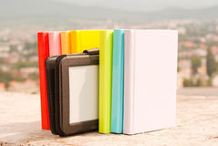 Row of colorful books with electronic book reader Stock Photos