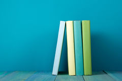 Row of colorful books, grungy blue background, free copy space. Row of books, grungy blue background, free copy space Vintage old hardback books on wooden shelf Stock Image