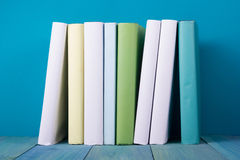 Row of colorful books, grungy blue background, free copy space. Row of books, grungy blue background, free copy space Vintage old hardback books on wooden shelf Stock Photos