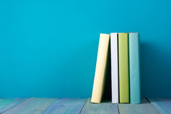 Row of colorful books, grungy blue background, free copy space. Row of books, grungy blue background, free copy space Vintage old hardback books on wooden shelf Royalty Free Stock Images