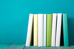 Row of colorful books, grungy blue background, free copy space. Row of books, grungy blue background, free copy space Vintage old hardback books on wooden shelf Stock Photo
