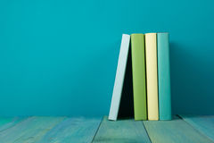 Row of colorful books, grungy blue background, free copy space. Row of books, grungy blue background, free copy space Vintage old hardback books on wooden shelf Royalty Free Stock Image