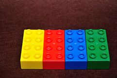 A row of colorful building blocks. Isolated on a brown background stock image