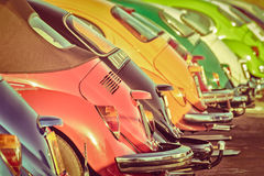 Row of colorful classic cars. Retro styled image of a row of colorful classic cars Stock Photos