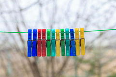 Row of colorful clothespins hanging on a green rope in a gerden Stock Images