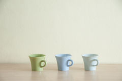 Row of colorful coffee cups on clear background Royalty Free Stock Images