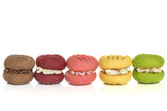 Row of Colorful Cream Cookies Isolated on White. Row of colorful cream cookies or maracoons, isolated on white Royalty Free Stock Photography