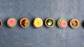 Row of colorful cupcakes on grey table Royalty Free Stock Photos