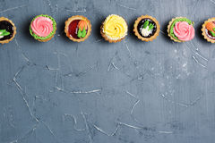 Row of colorful cupcakes on grey table Royalty Free Stock Image