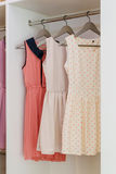 Row of colorful dress hanging in white wardrobe Royalty Free Stock Photography