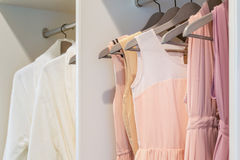 Row of colorful dress hanging in white wardrobe Stock Photos