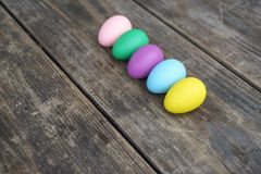 Row of colorful eggs on wooden table Stock Photo