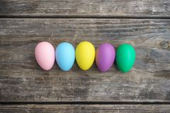 Row of colorful eggs on wooden table Stock Photography