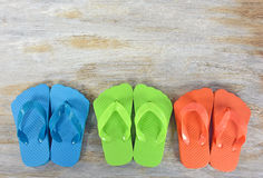 Row of colorful flip-flops on wood Royalty Free Stock Images