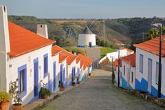A row of colorful houses along a steep cobbled street inside Odeceixe near Aljezur, leading to a whitewashed traditional windmil stock image