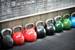 Row of colorful kettlebell weights in a gym Stock Photos