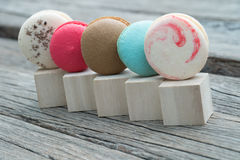 Row of colorful macaroons on wooden block. And table Royalty Free Stock Image