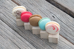 Row of colorful macaroons on wooden block. Row of colorful macaroons on wood block Stock Images